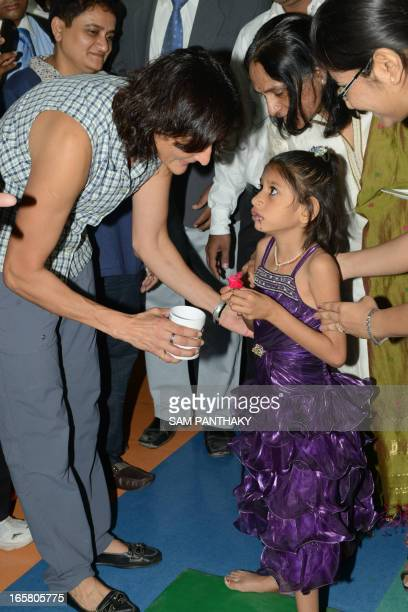 US astronaut of IndianSlovenian origin Sunita Williams interacts with a young girl during her visit to the Polio Foundation in Ahmedabad on April 6...