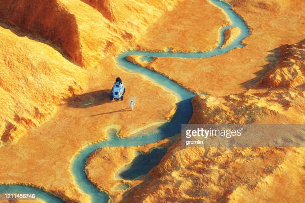 astronaut on distant exo planet with water - rock formation stock pictures, royalty-free photos & images