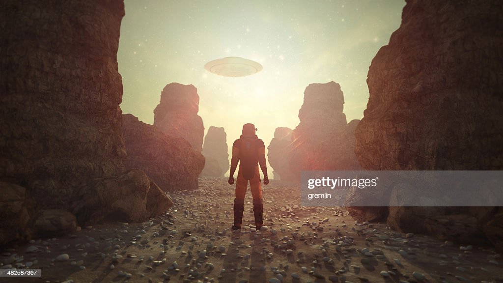 Astronaut on distant planet discovering UFO : Stock Photo