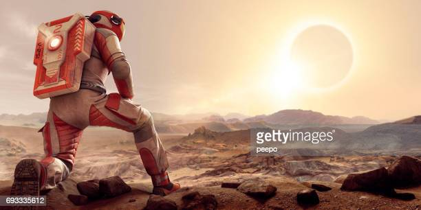 astronaut on mars kneeling and watching eclipse at sunset - solar system stock pictures, royalty-free photos & images