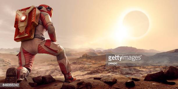 astronaut on mars kneeling and watching eclipse at sunset - mars stock pictures, royalty-free photos & images