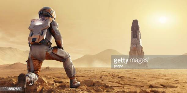 astronaut on mars kneeling looking at space rocket in distance - copy space stock pictures, royalty-free photos & images