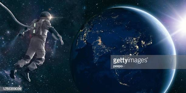 astronaut on space walk looks at lights of planet earth - copy space stock pictures, royalty-free photos & images