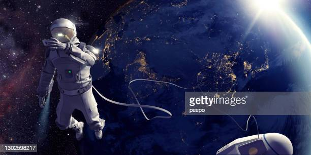 astronaut on spacewalk taking selfie in front of earth - astronaut stock pictures, royalty-free photos & images