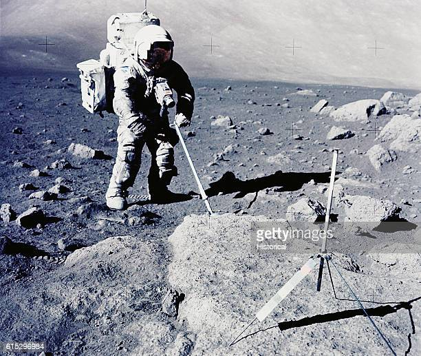 Astronaut on the Moon collecting lunar samples with an adjustable sampling scoop The rod mounted on a tripod is a gnomon which serves as an indicator...