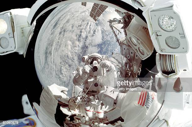 Astronaut Peter JK Wisoff Is Reflected In The Helmet Visor Of Astronaut Michael LopezAlegria As The Sts92 Mission Specialist Snapped This 35Mm Image...