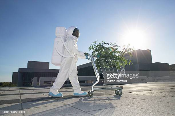 Astronaut pushing shopping trolley filled with pot plants, outdoors