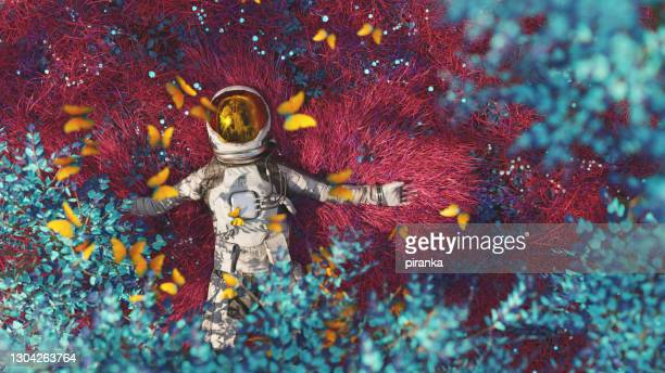 astronaut resting on an alien planet - astronaut stock pictures, royalty-free photos & images