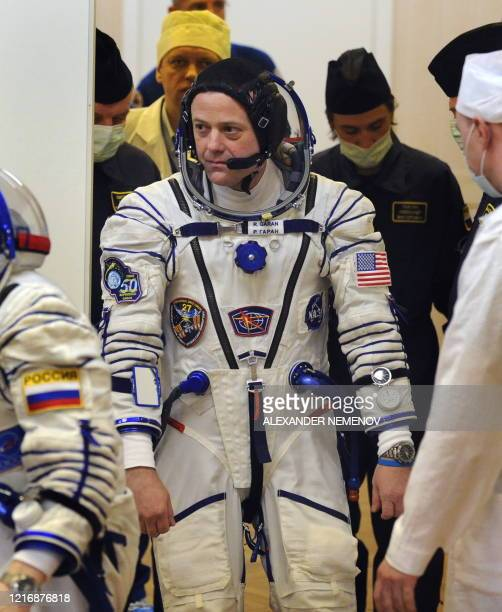 Astronaut Ron Garan enters a room during a space suit testing prior to blast off on Russian Soyuz TMA-21 rocket with other International Space...