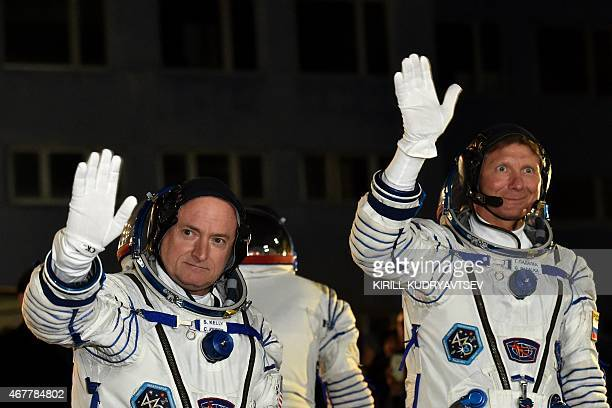 US astronaut Scott Kelly and Russian cosmonaut Gennady Padalka wave after their space suits were tested at the Russianleased Baikonur cosmodrome late...