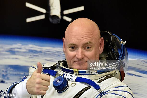 US astronaut Scott Kelly gestures as his space suit is tested at the Russianleased Baikonur cosmodrome prior to blasting off to the International...