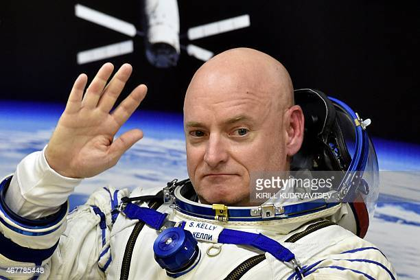 US astronaut Scott Kelly waves as his space suit is tested at the Russianleased Baikonur cosmodrome prior to blasting off to the International Space...