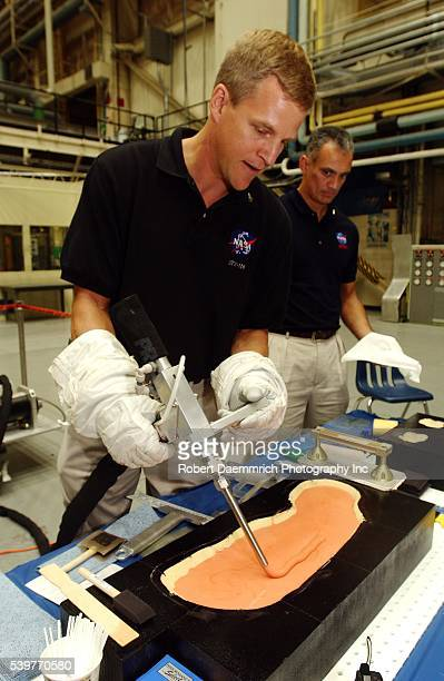 Astronaut Scott Parazynski who will possibly fly on upcoming STS118 demonstrates how tile filler material will be used to fill holes in space shuttle...