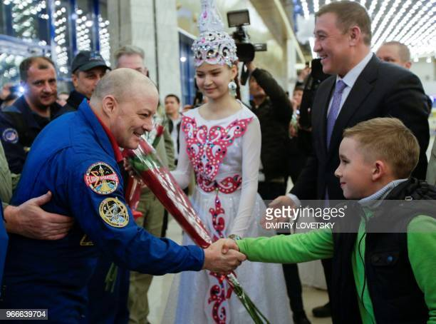 US astronaut Scott Tingle shakes hands with a local boy after the landing of the Russian Soyuz MS07 space capsule at Karaganda's airport on June 3...