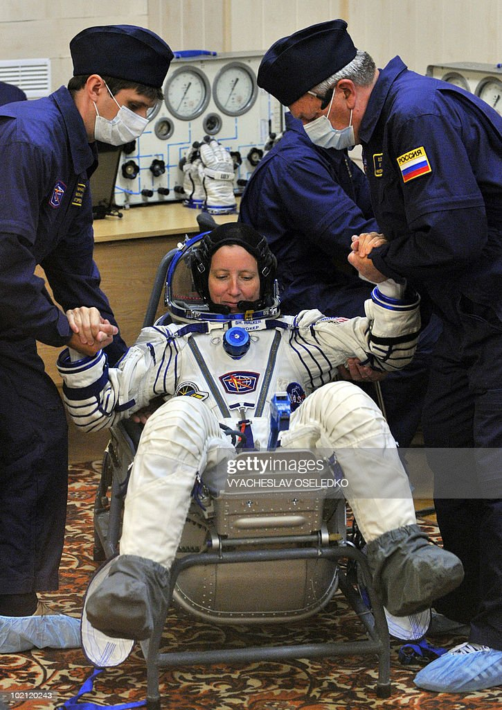 US astronaut Shannon Walker gets placed into her space suit at the Kazakhstan's Russian-leased Baikonur cosmodrome on June 15, 2010.
