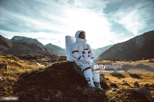 astronaut sitting by rock on land against mountain - space suit stock pictures, royalty-free photos & images