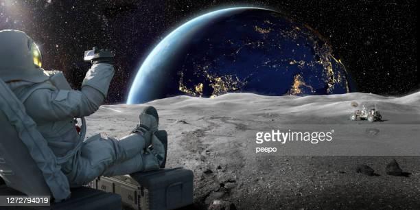 astronauta seduto sulla luna che registra l'alba sulla terra con lo smartphone - luna foto e immagini stock