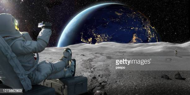 astronaut sitting on moon recording sunrise on earth with smartphone - copy space stock pictures, royalty-free photos & images