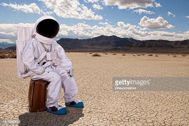 Astronaut sitting on suitcase in desert