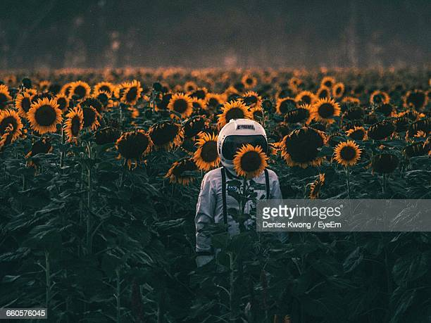 astronaut standing amidst sunflowers blooming on field - astronauta fotografías e imágenes de stock