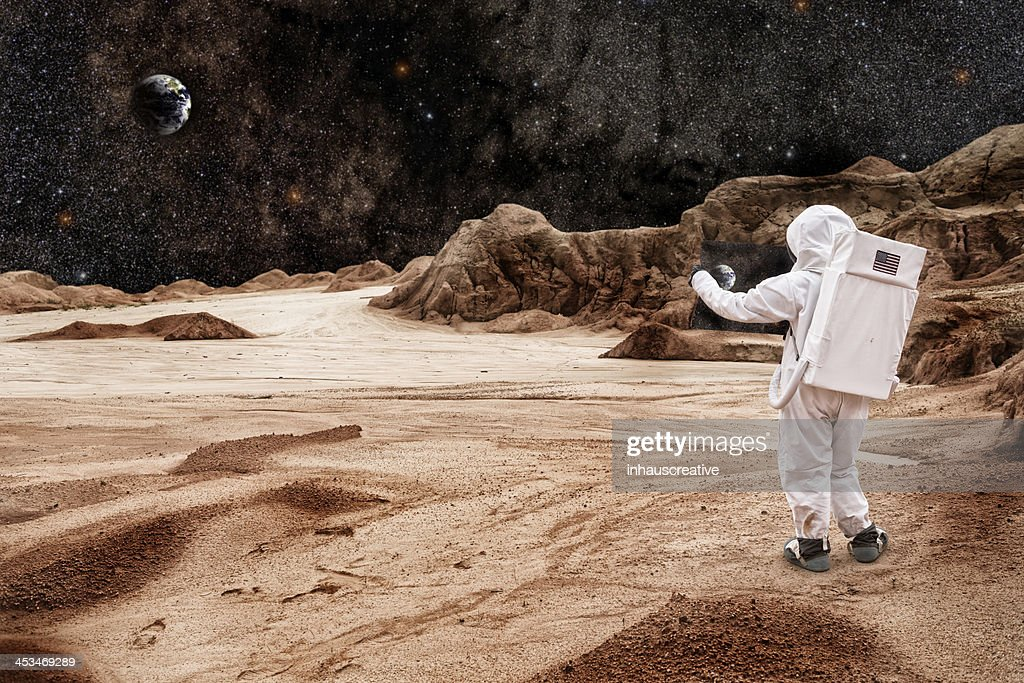 Astronaut Studying Map On Mars or the Moon : Stock Photo