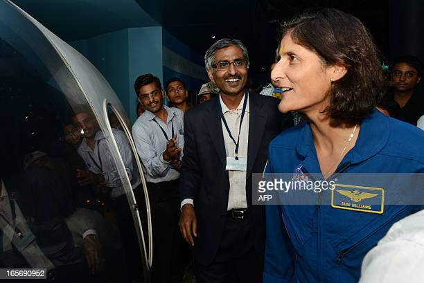 US astronaut Sunita Williams admires a model of a space ship during her visit at the Gujarat Science City on the outskirts of Ahmedabad on April 5...