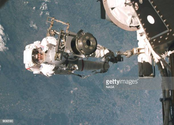 Astronaut Tamara Jernigan backdropped against the earth totes part of a Russianbuilt crane called Strela May 30 1999 Jernigan's feet are anchored on...