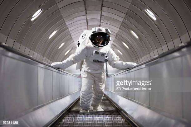 astronaut using an escalator - astronaut stock-fotos und bilder
