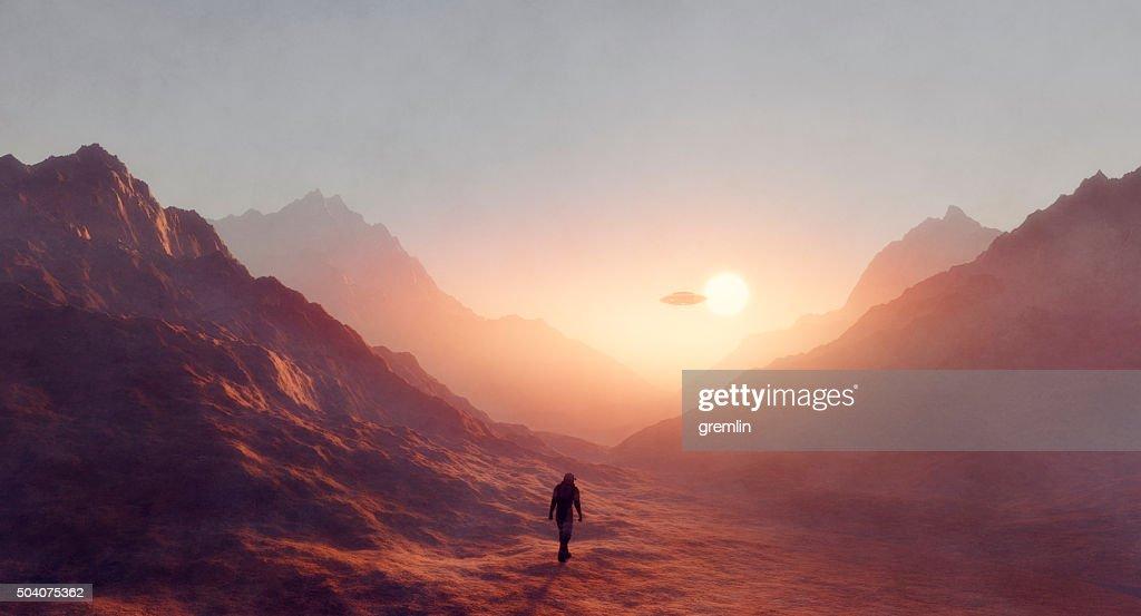 Astronaut walking on Mars, UFO flying : Stock Photo