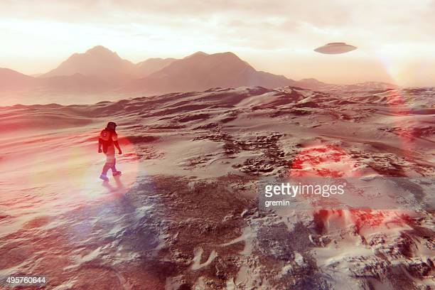 Astronaut walking on Martian surface, UFO flying