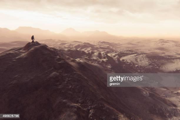 astronaut walking on smaller martian mountain ridge - extrasolar planet stock pictures, royalty-free photos & images