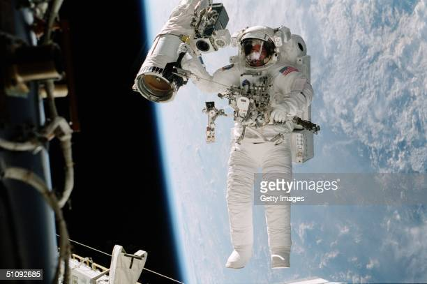 Astronaut William Mcarthur Appears Suspended Over The Blue And White Earth October 15 2000 During Space Walk Activities Near The Longerons Of The...