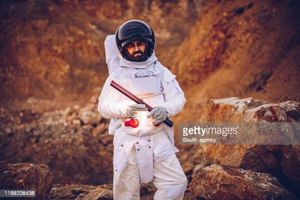 astronaut with lamp alone on mars - space helmet stock pictures, royalty-free photos & images