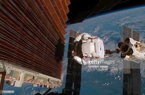 Astronaut works on the port overhead solar array wing on the International Space Station's P6 truss during the mission's fourth spacewalk.