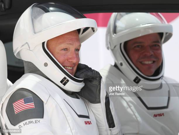 Astronauts Bob Behnken and Doug Hurley sit in a Tesla vehicle after walking out of the Operations and Checkout Building on their way to the SpaceX...