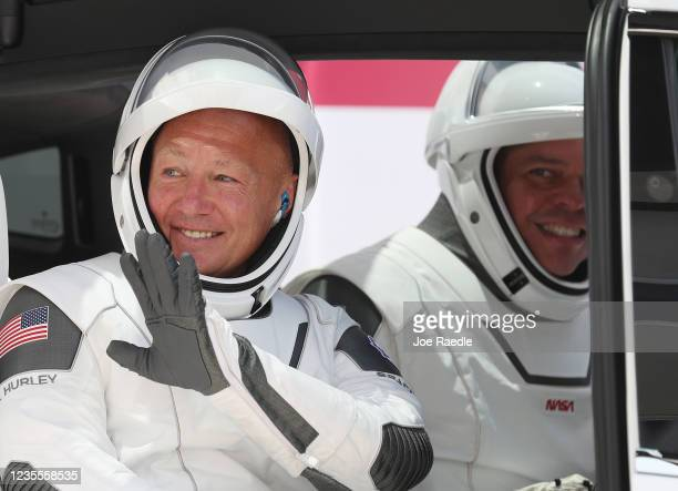 NASA astronauts Bob Behnken and Doug Hurley sit in a Tesla vehicle after walking out of the Operations and Checkout Building on their way to the...