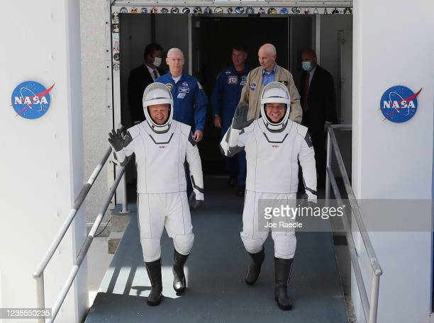 NASA astronauts Bob Behnken and Doug Hurley walk out of the Operations and Checkout Building on their way to the SpaceX Falcon 9 rocket with the Crew...