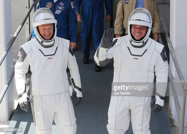 Astronauts Bob Behnken and Doug Hurley walk out of the Operations and Checkout Building on their way to the SpaceX Falcon 9 rocket with the Crew...