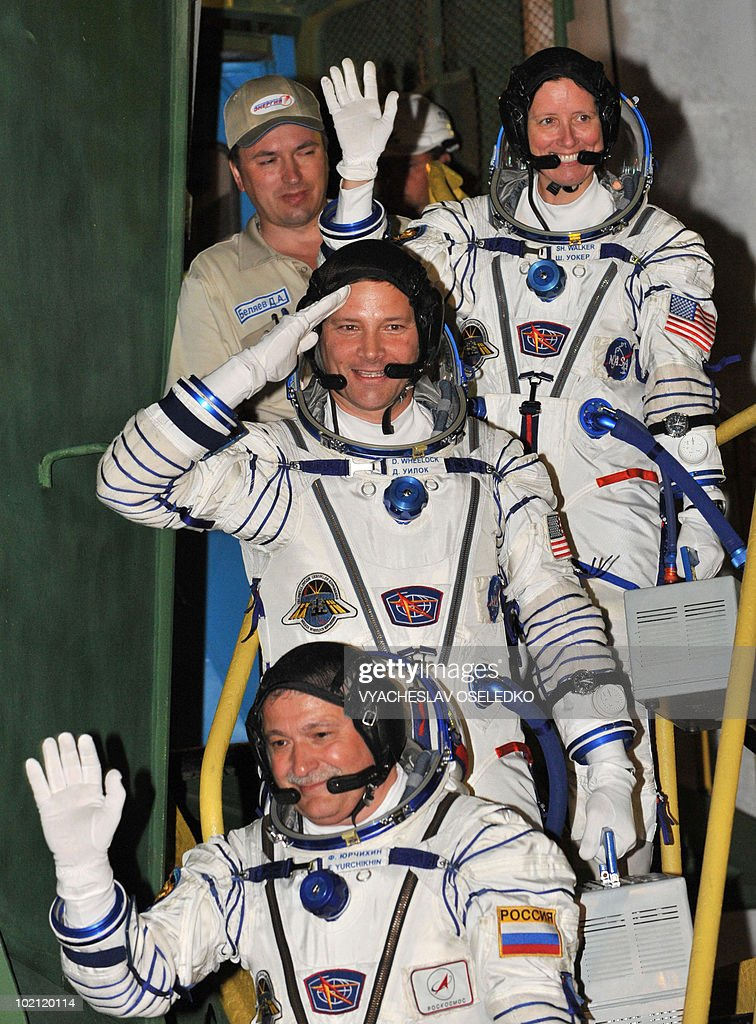 US astronauts Doug Wheelock (C), Shannon Walker (Top) and Russian cosmonaut Fyodor Yurchikhin (front) wave while boarding a Russian Soyuz TMA-19 rocket at Kazakhstan's Russian-leased Baikonur cosmodrome on June 15, 2010.