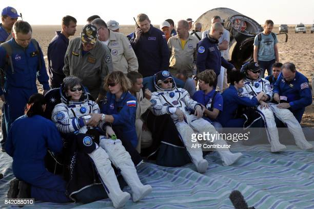 US astronauts Jack Fischer Peggy Whitson and Russian cosmonaut Fyodor Yurchikhin rest shortly after landing via the Russian Soyuz MS04 space capsule...
