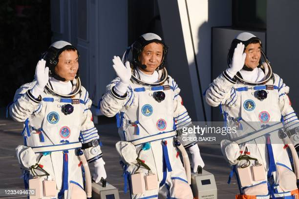 Astronauts Nie Haisheng , Liu Boming and Tang Hongbo wave during a departure ceremony before boarding the Shenzhou-12 spacecraft on a Long March-2F...