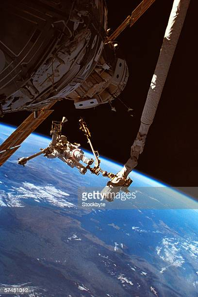Astronauts working on a satellite in space