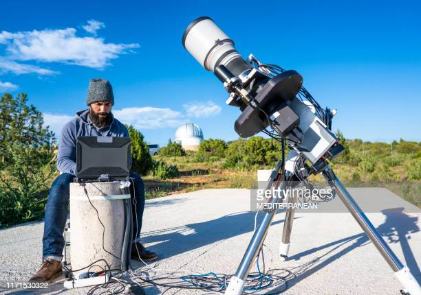 astronomer connecting telescope and computer - astronomy stock pictures, royalty-free photos & images