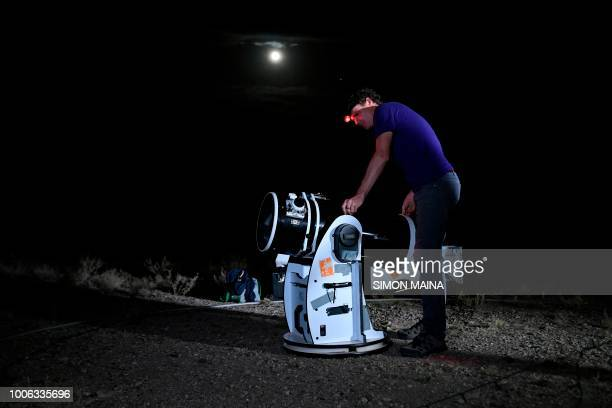 Astronomer Daniel Chu Owen from the Travelling Telescope company sets up a telescope to watch a 'blood moon' eclipse in Oloika town in Magadi Kenya...