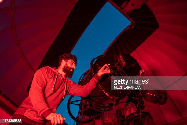 astronomer in photo telescope dome - astrophysics stock pictures, royalty-free photos & images