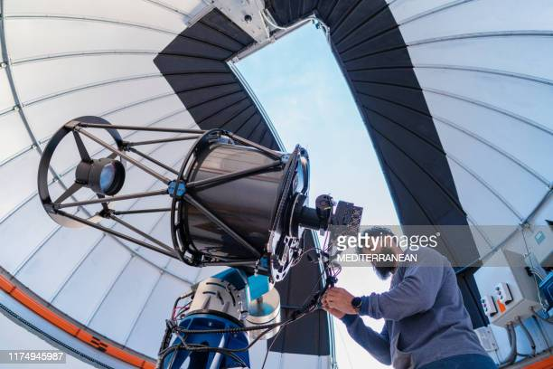 astronomer in photo telescope dome - physics stock pictures, royalty-free photos & images