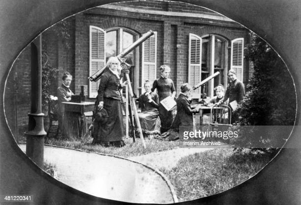 Astronomer Maria Mitchell standing second from left next to a telescope is shown with her astronomy class outside the observatory at Vassar College...