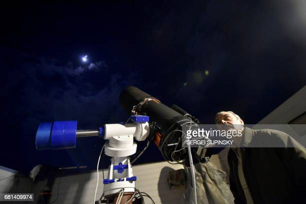 Astronomer Yaroslav Romanyuk looks through a telescope during his research in a small observatory not far from Kiev on March 7 2017 Perched...