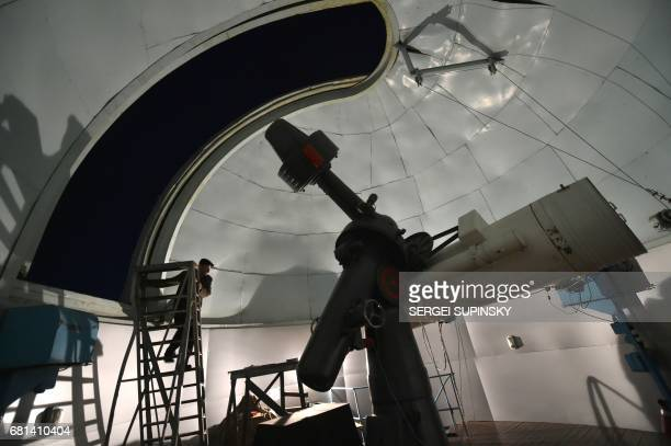 Astronomer Yaroslav Romanyuk prepares a telescope during his research in a small observatory not far from Kiev on March 7 2017 Perched spectacularly...