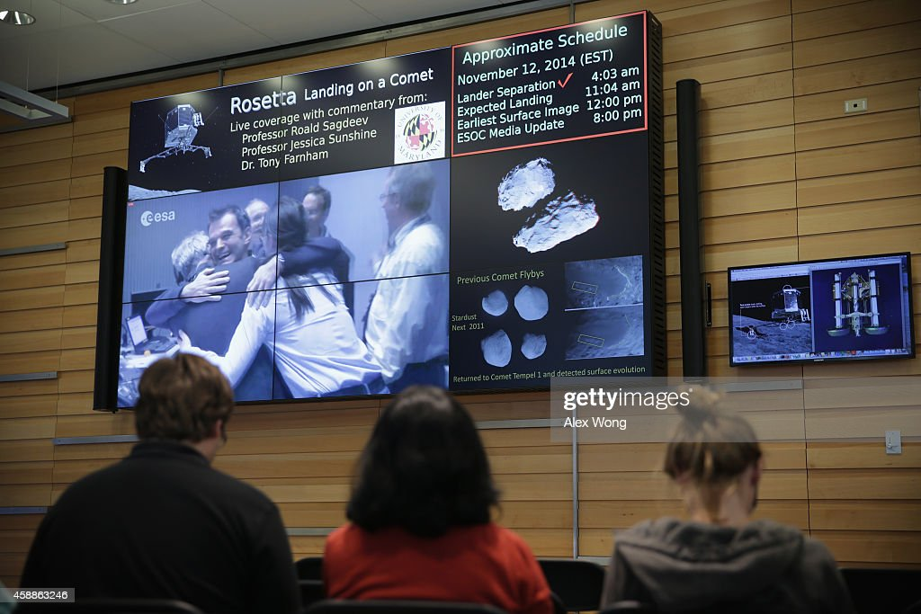Astronomers watch broadcast from a control room of the European Space Agency that monitors the Rosetta mission as scientists are seen celebrating of a safe landing during a landing viewing party November 12, 2014 at University of Maryland in College Park, Maryland. The Rosetta has successfully landed on the comet after sailing through space for more than 10 years.